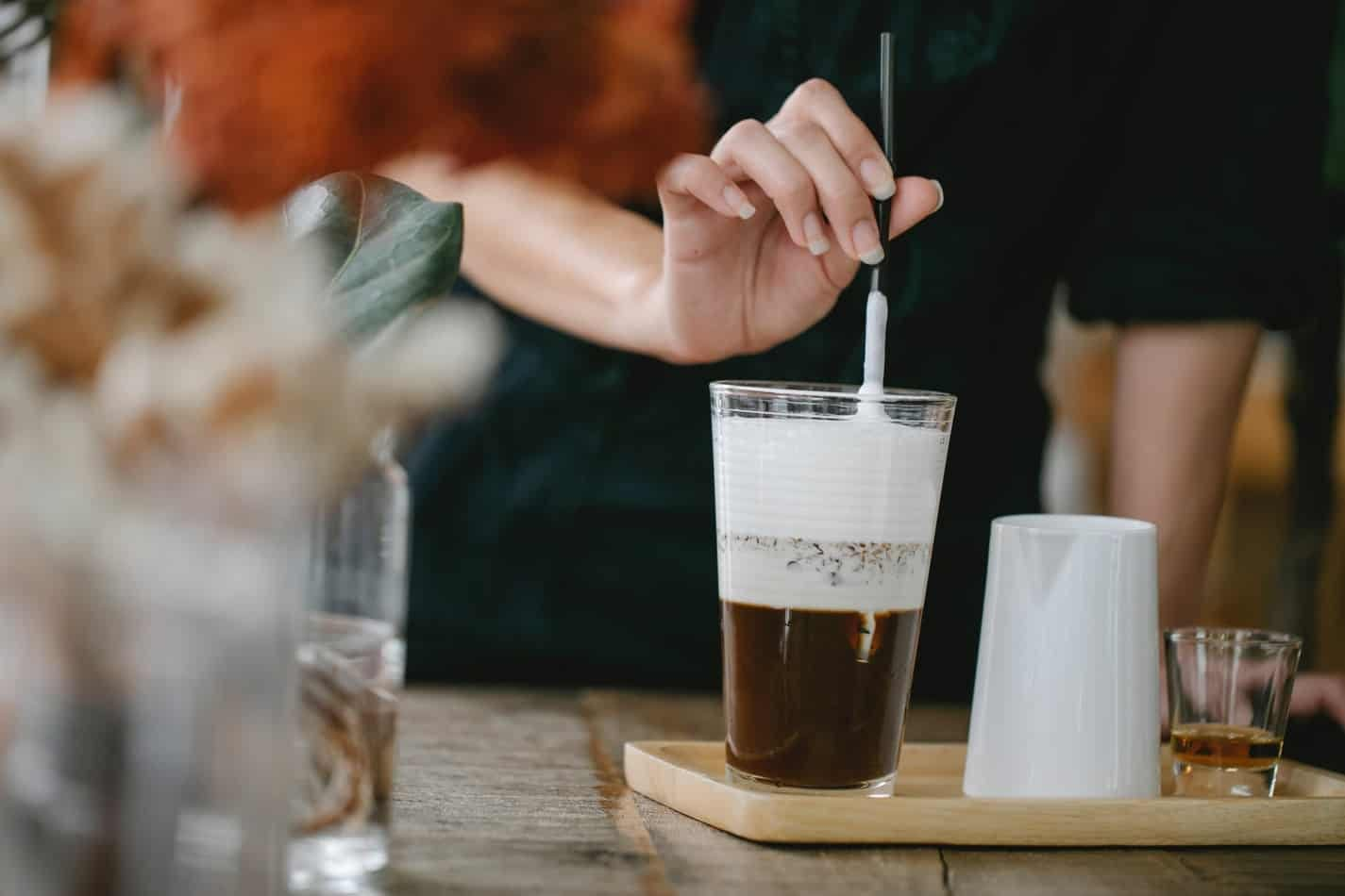 crop unrecognizable woman putting straw in glass of iced latte