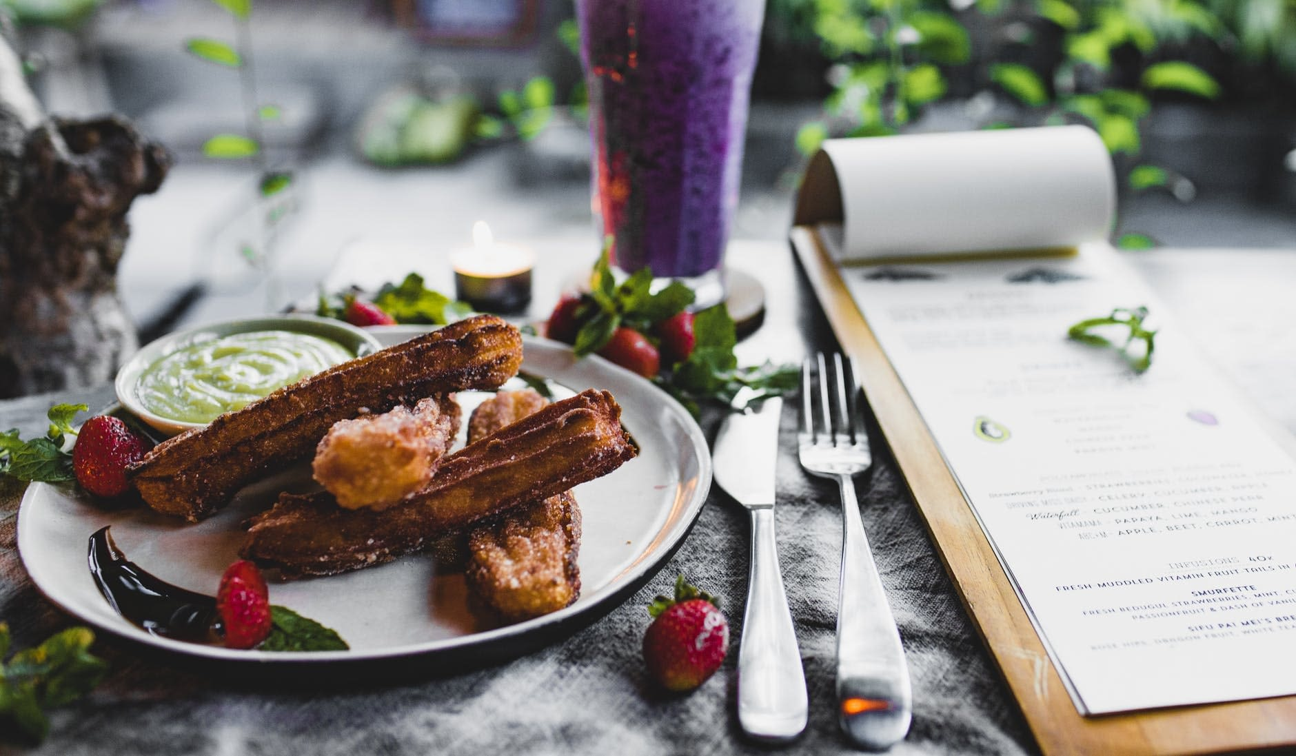 plate of delicious churros with sauce served on table with smoothie