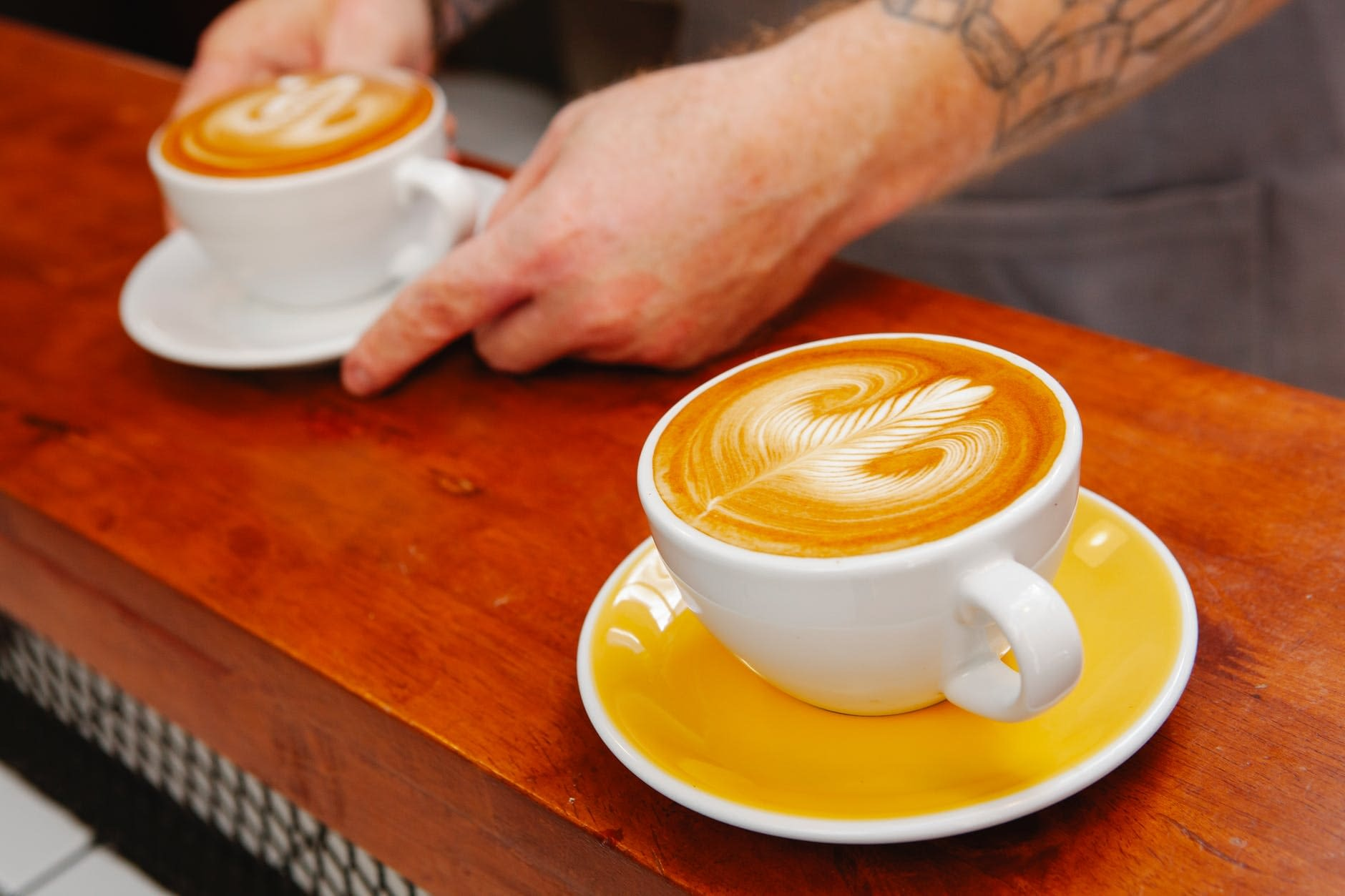 crop barista serving cups with delicious latte at counter