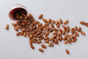 raw almonds spilled out of small ceramic bowl
